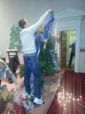 Adam decorates the tree in the main hall